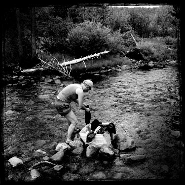 A woman washes clothes in a river in the Wasatch National Forest.