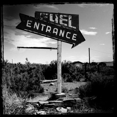 A worn sign which points toward the entrance of a petrol station on Route 191 in rural Utah.