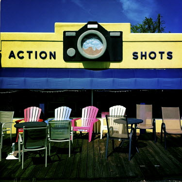 A shop sign on the office of a photographer's studio called 'Action Shots' with deckchairs arranged in front of the shop.