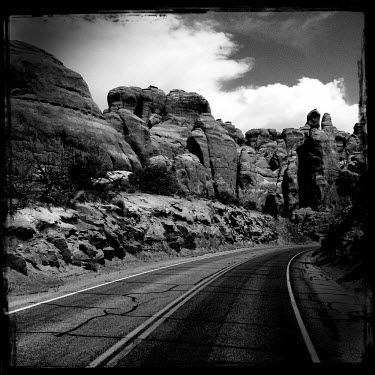 A road running through the Arches National Park passes rock formations on either side.