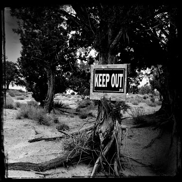 A sign on a tree reads 'Keep Out'.