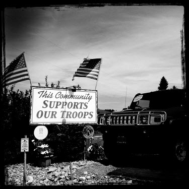 A sign which reads 'This Community Supports Our Troops.' stands at the entrance to Don K's car dealership in Whitefish next to a Hummer.