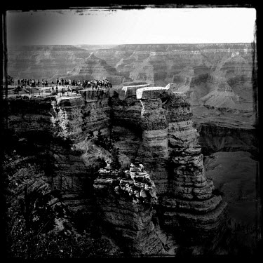 People stand on a rocky outcrop viewing platform in the Grand Canyon National Park.