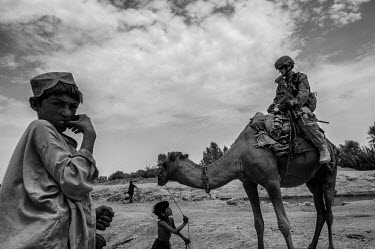 A US marine sits on a camel led by a child as he participates in a security patrol.
