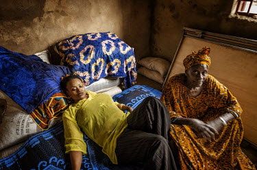 Oumou Sangare relaxes on cushions on the ground at her mother's (right) house in rural Mali.