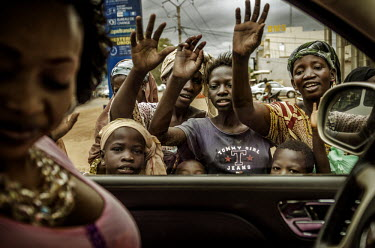 A group of locals wave at Oumou Sangare as she drives around Bamako. Sangare is one of Mali's biggest stars and has become internationally renowned for her singing of traditional Wassoulou music, a mu...