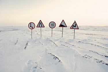 A group of roadsigns on an ice-road built to serve gas and oil companies exploring in the Nenets Autonomous Region in the Russian Arctic. In the summer the road will melt away revealing the marshland...