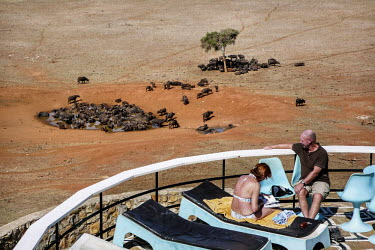 Tourists relax at their lodge overlooking buffalo at an artifical drinking well in Tsavo East National Park.