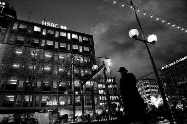 A man in a hat and coat walks past the offices of the private banking arm of British bank HSBC on Geneva's waterfront in the evening.