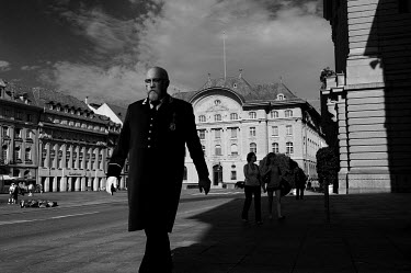 A huissier for the Federal Council walks on Bundesplatz (Parliament Square). Behind him is the Swiss National Bank building and the the Parliament just visible on the right.