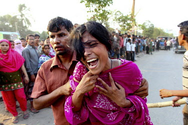 A woman cries while held by a man in front of the collapsed Rana Plaza complex in Savar. A large crowd of onlookers gathers in front of the collapsed Rana Plaza complex in Savar. The 8 storey building...