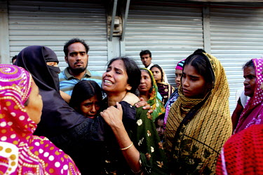 Women cry in front of the collapsed Rana Plaza complex in Savar near Dhaka. The 8 storey building, which housed a number of garment factories employing over 3,000 workers, collapsed on 24 April 2013....