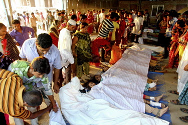 Relatives gather next to the bodies of some of the hundreds of workers killed in the collapsed Rana Plaza complex which are lined up on the floor, covered with white sheeting. The 8 storey building, w...