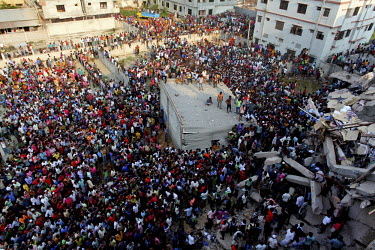 A large crowd of onlookers gathers in front of the collapsed Rana Plaza complex in Savar. The 8 storey building, which housed a number of garment factories employing over 3,000 workers, collapsed on 2...