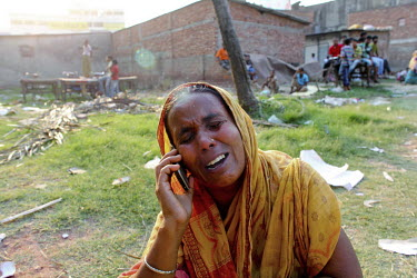 A woman cries as she speaks on the phone in front of the collapsed Rana Plaza complex in Savar. A large crowd of onlookers gathers in front of the collapsed Rana Plaza complex in Savar. The 8 storey b...