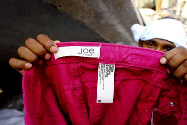 A man holds up a garment with a label of the Canadian clothing retailer Joe Fresh in the wreckage of the Rana Plaza complex in Savar. The 8 storey building, which housed a number of garment factories...