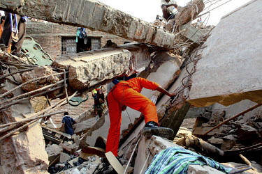 Rescue workers look for survivors in the collapsed wreckage of the Rana Plaza complex in Savar. The 8 storey building, which housed a number of garment factories employing over 3,000 workers, collapse...
