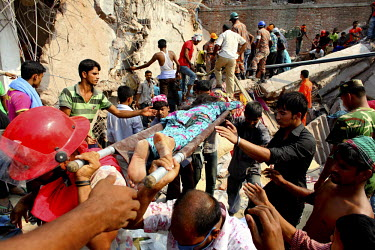 A woman is pulled from the rubble of the Rana Plaza complex in Savar by rescuers and civilian helpers. The 8 storey building, which housed a number of garment factories employing over 3,000 workers, c...