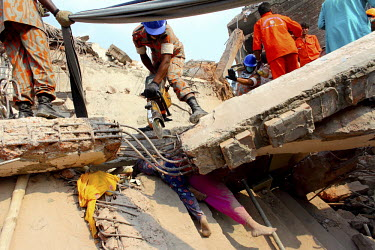 Rescue workers use steel cutting equipment to cut their way through parts of the collapsed Rana Plaza complex in Savar. The legs of two women crushed to death underneath the rubble are visible below....