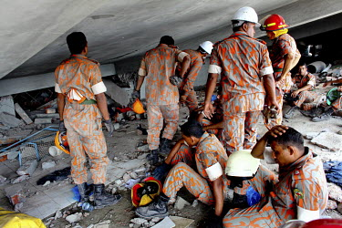 Rescue teams search for survivors on one of the floors of the collapsed Rana Plaza complex in Savar. The 8 storey building, which housed a number of garment factories employing over 3,000 workers, col...