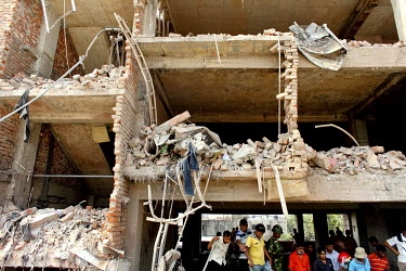 Rescue workers look for survivors in the collapsed shell of the Rana Plaza complex in Savar. The 8 storey building, which housed a number of garment factories employing over 3,000 workers, collapsed o...