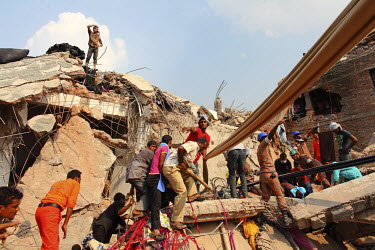 Rescue workers and their helpers look for survivors in the rubble of the collapsed Rana Plaza complex in Savar. The 8 storey building, which housed a number of garment factories employing over 3,000 w...