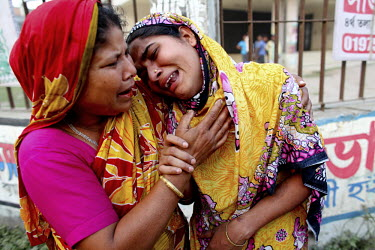 Two women cry for their dead and missing relatives outside the collapsed Rana Plaza complex in Savar. The 8 storey building, which housed a number of garment factories employing over 3,000 workers, co...