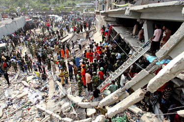 Rescue teams use ladders to access one of the floors of the collapsed Rana Plaza complex in search of survivors while onlookers wait. The 8 storey building, which housed a number of garment factories...