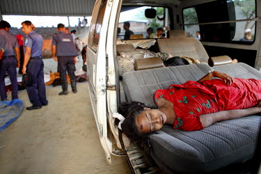 A dead female worker lies on a car seat outside the Rana Plaza complex while rescue workers look for other survivors. The 8 storey building, which housed a number of garment factories employing over 3...