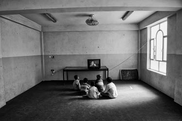 A group of young boys sit on the floor in an orphanage's bare room and watch television.
