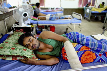 22 year old Shahidul lies in a hospital bed in the Pongu Hospital in Dhaka with his injured arm bandaged up. He is one of the survivors of the collapse of the Rana Plaza complex. The 8 storey Rana Pla...