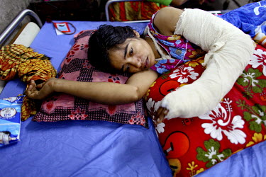 Razia is one of the survivors of the collapsed Rana Plaza complex. She is resting on her bed in the Pongu Hospital in Dhaka with her injured left arm. She has severe pain even after 20 days of treatme...