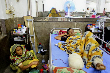 One of the survivors of the collapsed Rana Plaza complex lies on his bed in the Pongu Hospital in Dhaka. He has lost part of his right leg. His wife crouches on the ground, washing dishes and caring f...