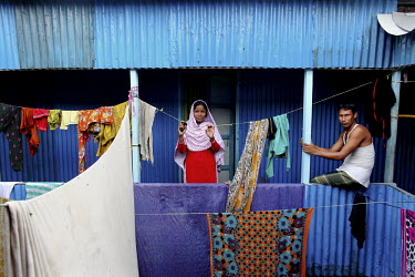 Bristy, 17, (left) stands outside a corrugated iron shack in Dhaka which she shares with five other garment workers to save money. She has been working in the garment industry since she was 13.