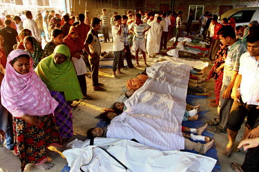 Relatives gather next to the bodies of some of the hundreds of workers killed in the collapsed Rana Plaza complex which are lined up on the floor, covered with white sheeting.The 8 storey Rana Plaza c...