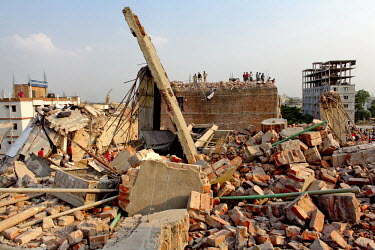 Rescue teams and civilian helpers search for survivors on one of the floors of the collapsed Rana Plaza complex in Savar.The 8 storey Rana Plaza complex, which housed a number of garment factories emp...