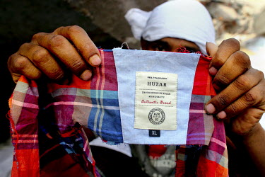 A man holds up a garment with a label of the Danish clothing retailer Huzar found in the ruins of the collapsed Rana Plaza complex on the outskirts of Dhaka. The 8 storey Rana Plaza complex, which hou...