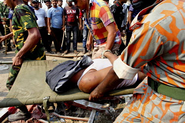 A man is pulled out of the rubble of the collapsed Rana Plaza complex in Savar on the outskirts of Dhaka by rescuers and army personnel. The 8 storey Rana Plaza complex, which housed a number of garme...