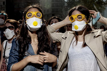 Two female protesters with yellow goggles and face masks stand amid a crowd of protesters in the centre of Istanbul.Protests against the government of Recep Tayyip Erdogan spread across Turkey after a...