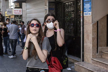 Two young women look on as tear gas canisters are fired by police at protesters during a protest. Protests against the government of Recep Tayyip Erdogan spread across Turkey after a peaceful sit in o...