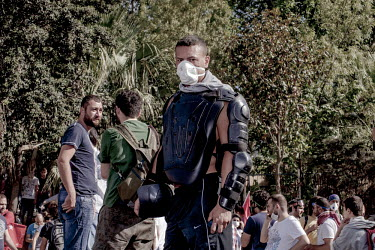 A protester wearing riot gear used by the Istanbul police service stands amid a crowd of other protesters in the Gezi Park area of central Istanbul. Protests against the government of Recep Tayyip Erd...