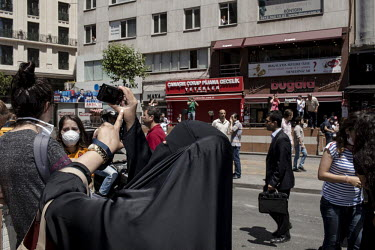An arab tourist takes pictures of protesters chanting calling on others to follow them to Taksim Square, the centre of the protest. Protests against the government of Recep Tayyip Erdogan spread acros...