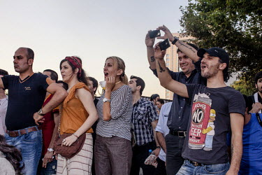 People chant and take pictures as they watch thousands of protesters gather in Taksim Square. Protests against the government of Recep Tayyip Erdogan spread across Turkey after a peaceful sit in organ...