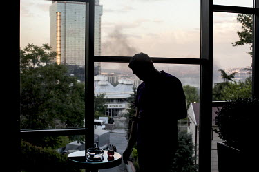 A man drinks tea at a hotel balcony that overlooks Gezi park and the Bosphorus sea. The smoke below is from the fires lit by anti-government protesters in the Besiktas neighborhood of Istanbul.Protest...