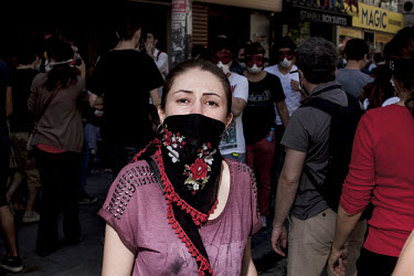 A protester with a scarf tied around her face shows the effects of tear gas fired by riot police in the Osmanbey district of Istanbul. Protests against the government of Recep Tayyip Erdogan spread ac...