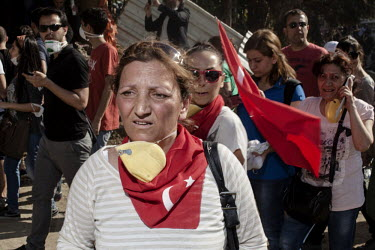 A protester with a a scarf and face mask around her neck shows the effects of tear gas fired by riot police in the Osmanbey district of Istanbul. Protests against the government of Recep Tayyip Erdoga...