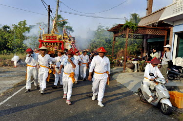 A group of men carry a huge model boat in procession around the island during a festival that honours its gods. The week-long event, that takes place every third year, culminates in the burning of the...