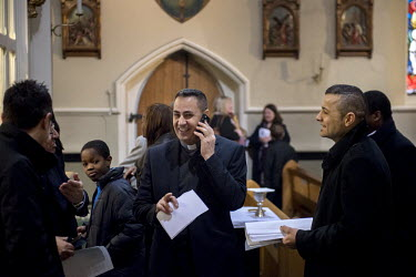 Father Nizar Semaan speaks on a mobile phone while he greets his congregation at Holy Trinity Catholic church in Brook Green, London. The church is the London centre for the Syriac Catholic Community...