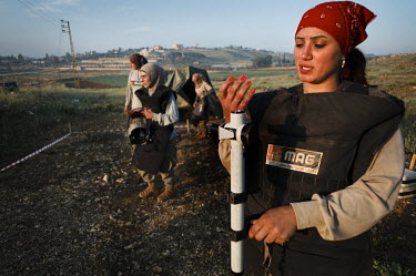 Fatima Bahmad, a deminer working for Mines Action Group (MAG), looks at her bright red finger nails while working with her colleagues from Battle Area Clearance (BAC) team 3, to clear an area of land...