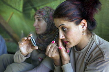 Fatima Bahmad, a deminer working for Mines Action Group (MAG), applies make-up while on her lunch break.